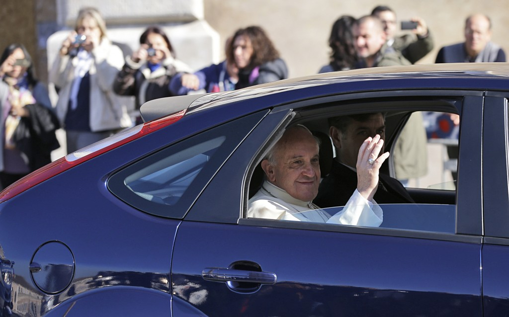 Pope Francis blesses the faithful from the back seat of his car as he leaves the Quirinale Presidential Palace in Rome after meeting with Italian President Giorgio Napolitano on Thursday. Pope Francis traveled across town Thursday for his first state visit with the Italian president, a traditionally pomp-filled ceremony that the simple pontiff defused by declining a mounted presidential guard escort and traveling in his own Ford Focus instead.