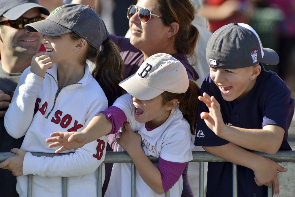 From left, Emma Jadul, 11, sister Caroline Jadul 7, both of Redding, Mass., and Christian Hoyt, 11, of Brockton, Mass., cheer Boston Red Sox players floating by on amphibious duck Bnoats during a rolling victory parade on the Charles River on Saturday in Cambridge Mass.
