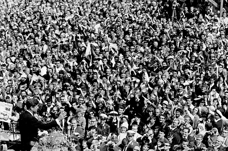 In this June 26, 1963 file photo, U.S. President John F. Kennedy, left, waves to a crowd of more than 300,000 gathered to hear his speech where he declared