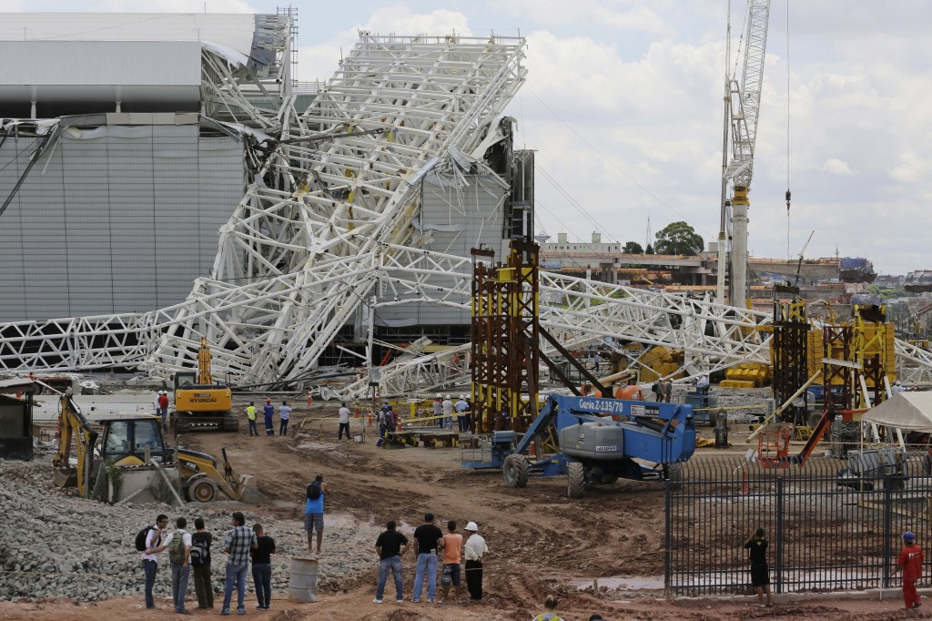 People stand in front of a metal structure that buckled on part of the Itaquerao Stadium in Sao Paulo, Brazil, on Wednesday.