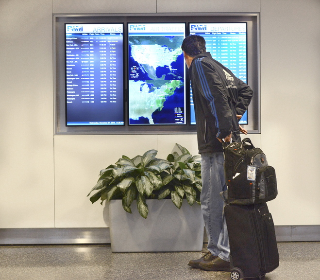 "Sumner Thompson of Phippsburg checks to make sure his Portland International Jetport flight is on time Wednesday. ""I fly every week, and this is quiet for even a normal weekday,"" Thompson said."