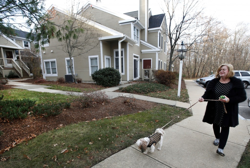 Barbara Kansky, condo manager of Devon Wood in Braintree, Mass., walks her dog, Justine, along a sidewalk on the 350-acre property. Kansky turned to DNA testing to identity lawn-fouling dogs, yielding immediate and dramatic results.