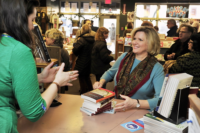 Jeanne Hulit, right, acting administrator of the Small Business Administration, buys books at Longfellow Books on Monument Square in Portland on Small Business Saturday.