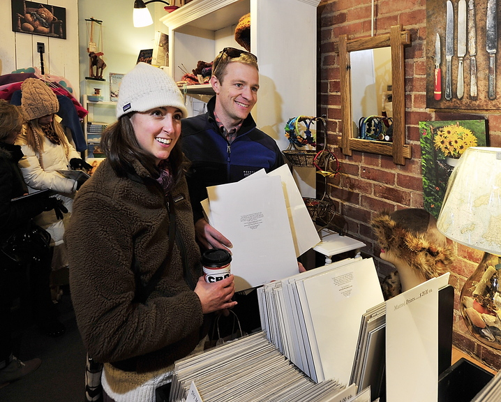 "Julie and Toby Walch of Scarborough look at photographs at Lisa-Marie's Made in Maine on Exchange Street in Portland on Saturday. ""It's what tourists want. They don't want something made in China,"" said Marie Stewart, the store manager."