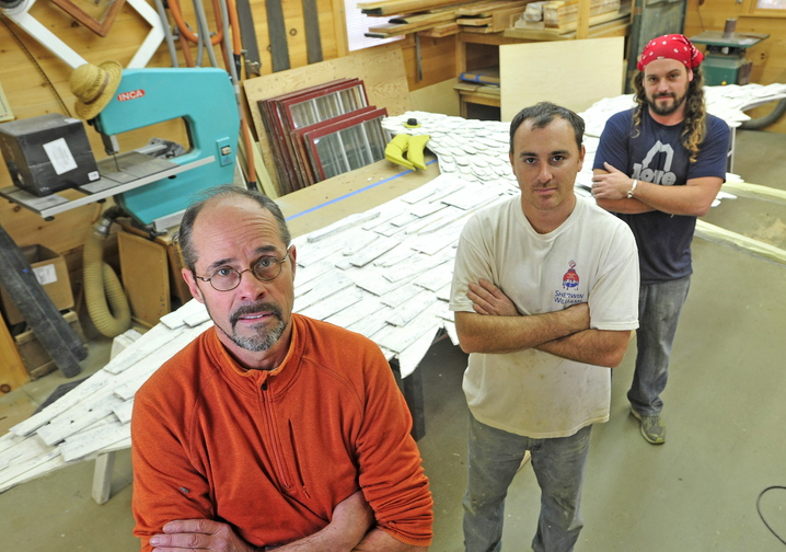 Stephen Dionne, left, with his employees Joe Almand, 33, center, and Dylan Daigle, 28, stand next to the 25-foot wooden seagull sculpture created by Skowhegan artist Bernard Langlais that they have restored.
