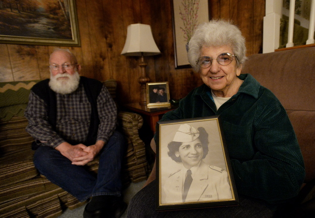 Pauline Young, a combat nurse in World War II and Korea, holds a photograph of herself in her dress uniform in 1942. To the left is friend and fellow veteran John Ames.