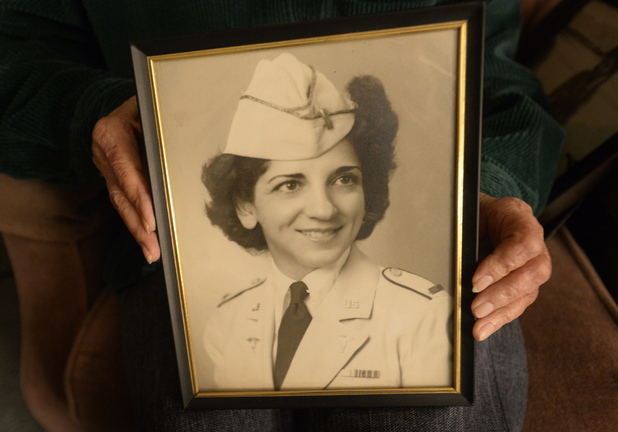 Shawn Patrick Ouellette/Staff Photographer Pauline Young, a nurse in World War II and Korea, holds a photograph of herself in her dress uniform in 1942.