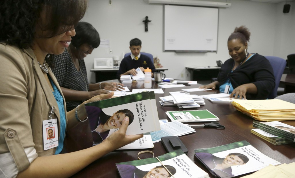 Houston city employee Lida Moreno, left, and colleagues count out Spanish language brochures for Enroll America in preparation for door-to-door distribution. Houston is trying to reach more than 1 million people who don't have health insurance.