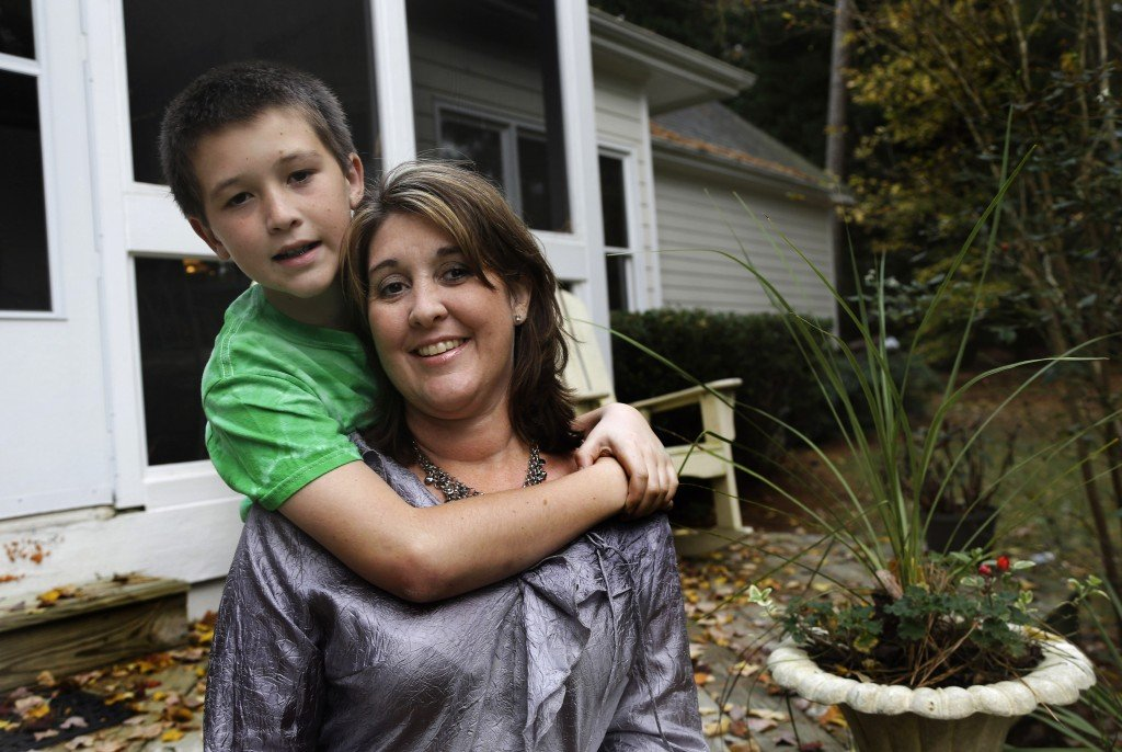 Jill Morin poses for a photo with her son Kyle at their home in Raleigh, N.C. Morin suffers from a serious heart condition and suffered a cardiac arrest in 2009. Morin and hundreds of thousands of other people with pre-existing chronic conditions who are covered through high-risk insurance pools will see their coverage dissolve by year's end. They are supposed to gain regular coverage under the Affordable Care Act.