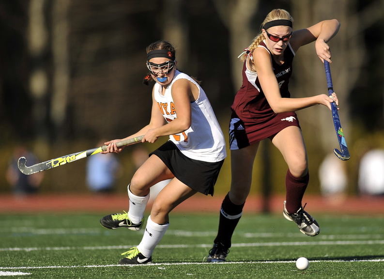 Gabe Souza/Staff Photographer NYA's Juliana Tardiff looks back toward the ball as Foxcroft's Amber Anderson makes a charge at it during the first half of the Class C field hockey championship at Yarmouth High School Saturday, November 2, 2013.
