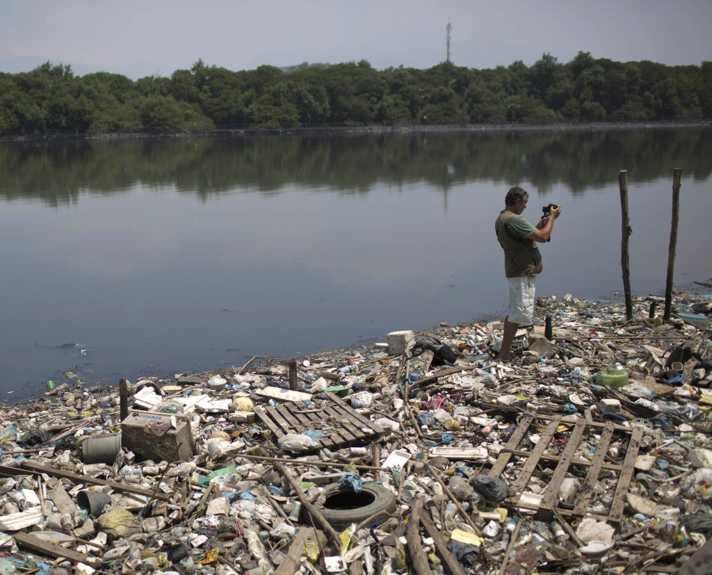 Biologist Mario Moscatelli takes photos of trash floating on the Canal do Fundao in Rio de Janeiro, Brazil, last month. Runoff from Rio's many slums and poor neighborhoods drain into waters soon to host some of the world's best athletes.