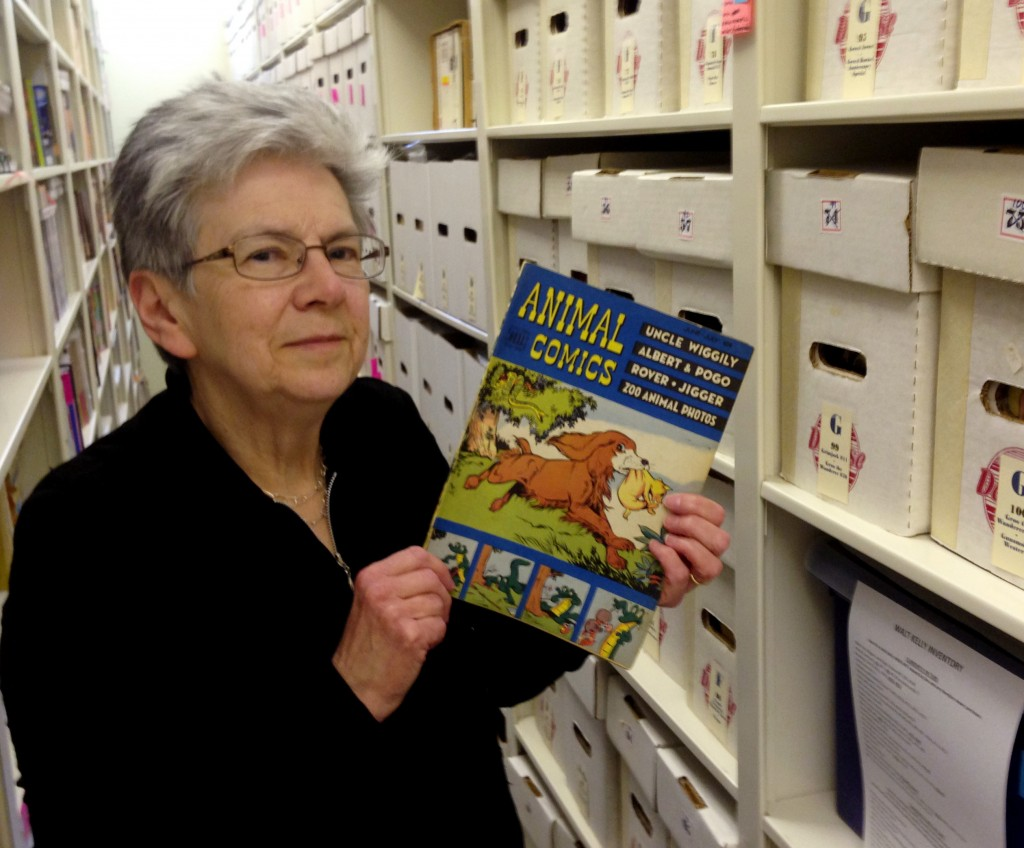 "Maggie Thompson shows off a copy of ""Animal Comics"" in the addition built onto her Wisconsin home to house her estimated tens of thousands of comic books."