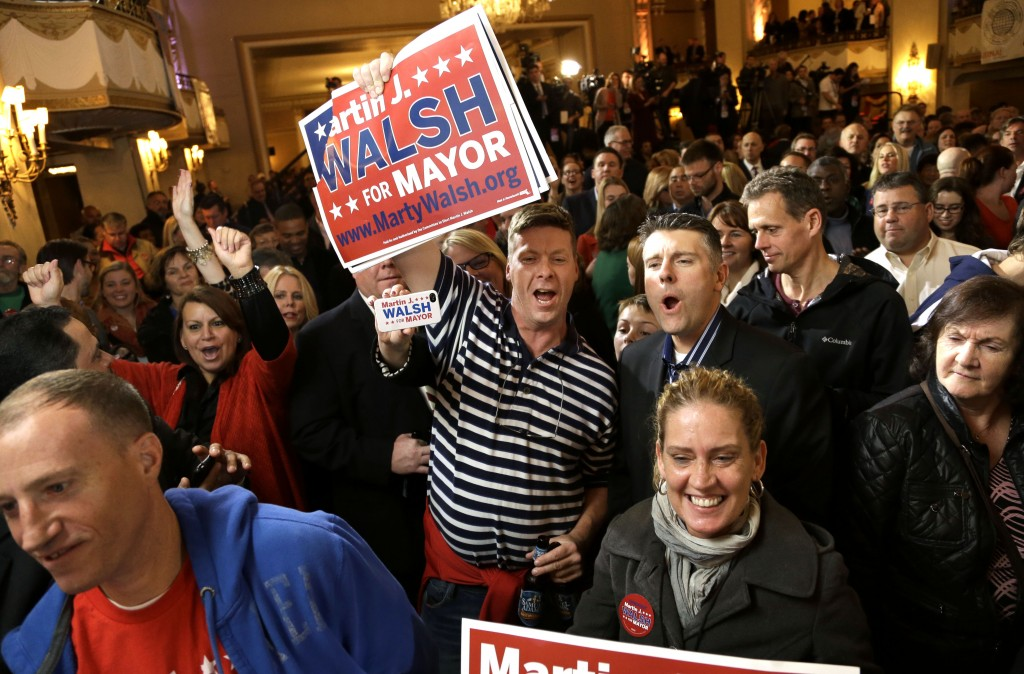 Martin Davis, of Weymouth, Mass., center, a Martin Walsh supporter, holds a placard while reacting to televised returns in the race for mayor of Boston during a watch party at a hotel in Boston, Tuesday, Nov. 5, 2013. Mass. State Rep. Martin†Walsh, D-Boston, and City Councilor John Connolly are running for the office held by Boston Mayor Thomas Menino for more than two decades.