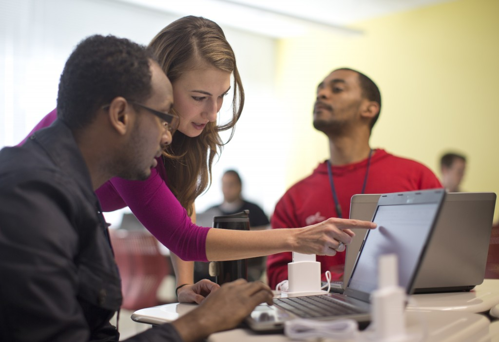 Kaylin Wainwright, center, works with student Natnael Gebremariam, left, at a computer during a General Educational Development test preparation class at the Sonia Gutierrez Campus of the Carlos Rosario International Public Charter School in Washington. Seated right is student Sibusiso Kunene.