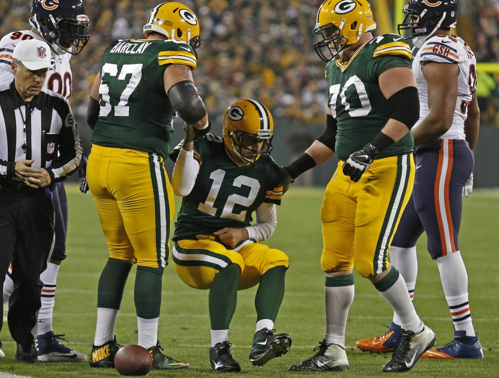 Green Bay Packers quarterback Aaron Rodgers is helped up by two of his offensive linemen, tackle Don Barclay (67) and guard T.J. Lang (70), after being injured on a play by Chicago Bears defensive end Shea McClellin during last Monday night's game in Green Bay, Wis.