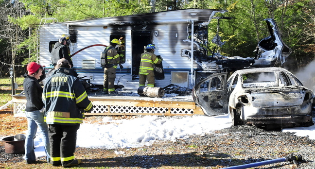 Laura Ellis, left, speaks with a firefighter as others extinguish the destroyed remains of a camper she was staying in Tuesday on Beach Road in South China. Ellis was staying at friend and owner Tim Elkin's camper when she started her car, right, which caught fire, then ignited the camper.