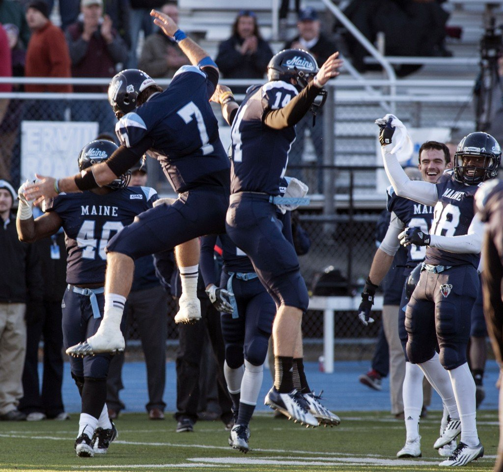"University of Maine quarterback Marcus Wasilewski (7) and teammate Daniel Collins (14) celebrate after defeating Rhode Island 41-0 in an NCAA football game in Orono on Nov. 16. Their team now holds a 10-1 record. Their success has caused ""a nice little bit of unity"" on campus, a student says."