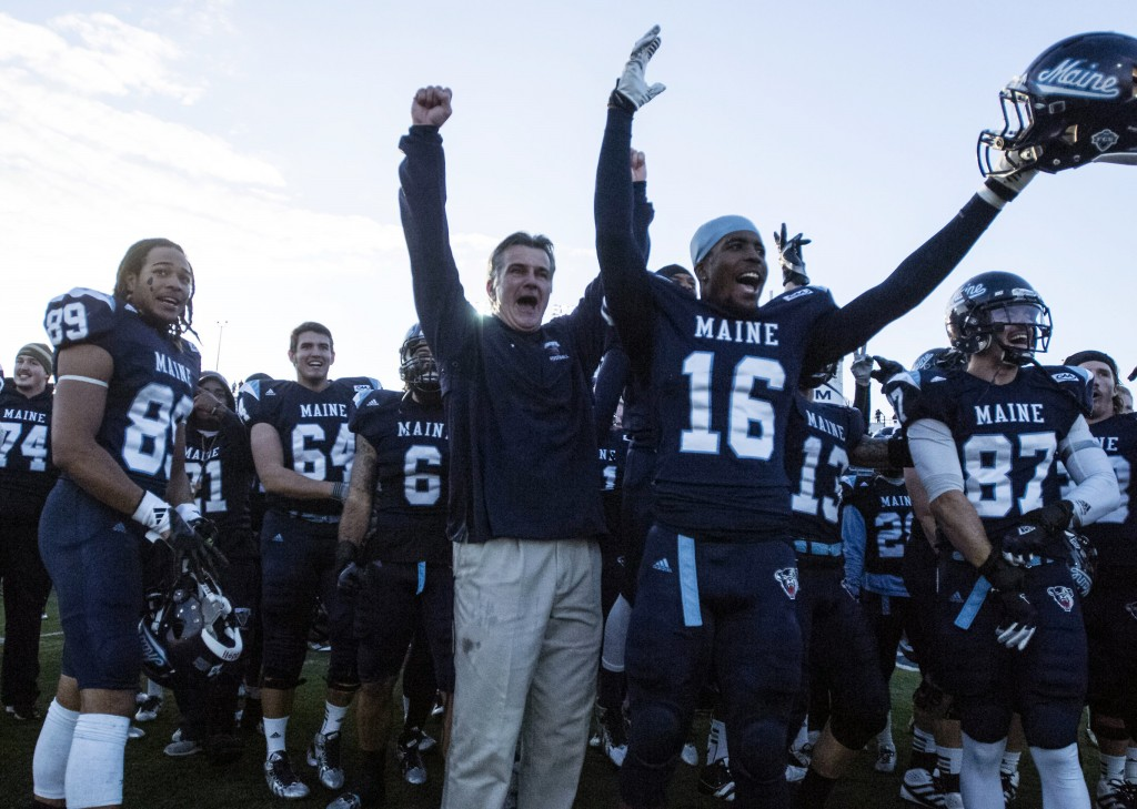 Maine football coach Jack Cosgrove celebrates with his players after defeating Rhode Island 41-0 in an NCAA football game in Orono, Maine, Saturday, Nov. 16, 2013. (AP Photo/Michael C. York)
