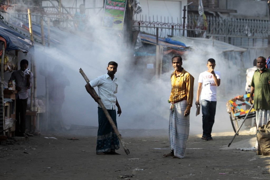 A Bangladeshi man armed with a bamboo stick reacts to the tear gas fired by police as people gathered for a protest in front of a closed factory in Gazipur, on the outskirts of Dhaka, Bangladesh, on Tuesday. Police fired rubber bullets and tear gas to disperse thousands of garment workers who rampaged through industrial towns in Bangladesh to protest the killing of two factory workers during a demonstration for higher wages. International retailers have been under pressure to improve conditions for workers.