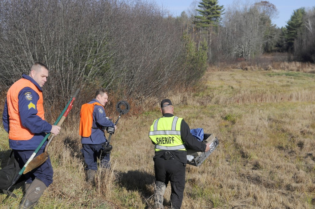 Maj. Ryan Reardon, right, of the Kennebec County Sheriff's Office, carries evidence collection tools; state police Detective Terry James, center, lugs a metal detector; and state police Detective Sgt. Jason Richards carries hand tools into the woods of Manchester on Saturday afternoon to excavate skeletal remains discovered by hunters earlier in the day. The sheriff's department was called just after 8 a.m. when a deer hunter encountered the bones about a half-mile up a dirt logging road from Puddledock Road, according to Reardon. The remains, believed to be of an adult, will be examined as they are recovered to determine an identity and a cause of death, Reardon said.