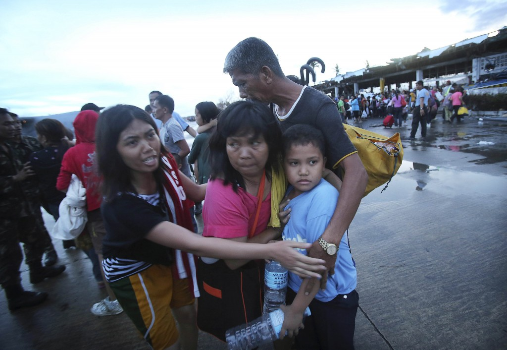 Survivors of Typhoon Haiyan comfort each other after not being allowed to board a C-130 cargo plane because of limited space, at the airport in Taclobanon Tuesday.
