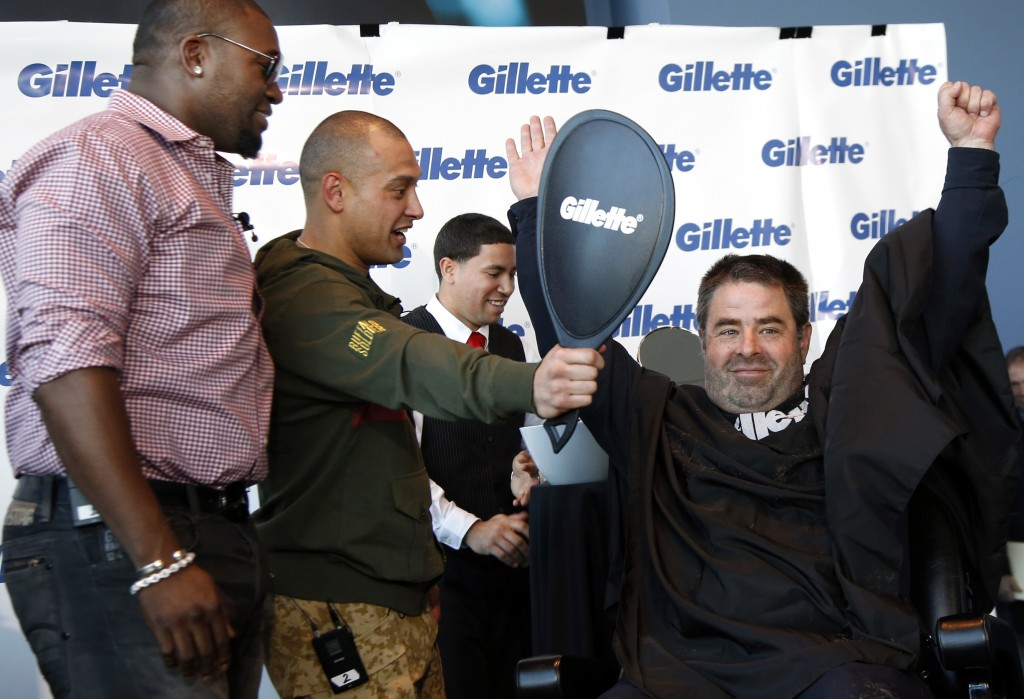 "Boston police officer Steve Horgan recreates his famous home run playoff pose as Red Sox players Shane Victorino, center, and David Ortiz watch during Gillette's $100,000 ""shave off"" fundraising event for One Fund Boston on Monday."
