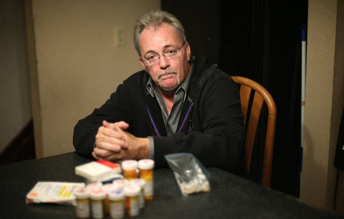 Mike Graham poses at his home in Manteno, Ill., with medications he used to take for degenerative disc disease. Graham began using medical marijuana about five years ago, which allowed him to stop using most of the pharmaceuticals for pain relief.