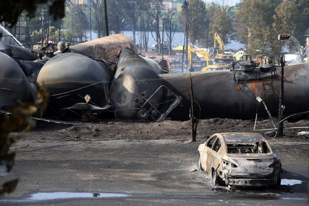 A burned out vehicle sits near the wreckage of tanker cars following the train derailment in Lac Megantic, Quebec, on July 7, 2013. U.S. railroads are supporting new safety standards for rail cars that haul flammable liquids to address flaws that can allow crude oil, ethanol and other substances to leak during accidents.