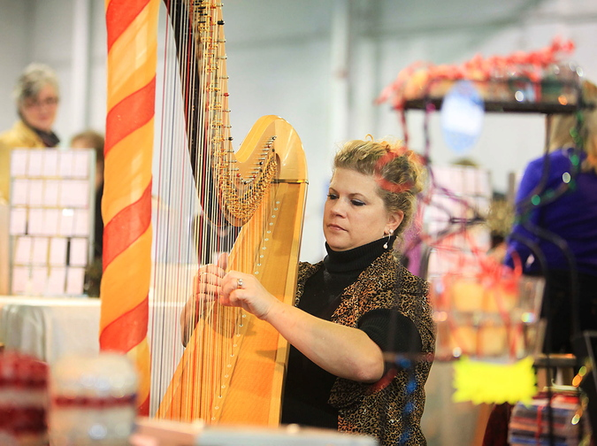 Mellori Worthen of Mercer, a professional orchestra and Celtic harpist, plays soothing holiday music on her harp for shoppers.