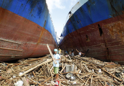 Residents pick up pieces of wood in between two cargo ships washed ashore four days after a super typhoon hit Anibong town, Tacloban city, central Philippines.