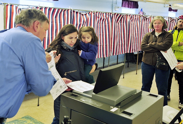 Voters wait patiently in line as Sarah Heeley, holding her daughter Charlotte Heeley, 2, gets help from a South Portland election clerk trying to get a voting machine to accept her ballots Tuesday. The warden at the American Legion Hall voting site for Ward 2, Precinct 1, said the machines were very slow processing the ballots, causing a long line of voters.