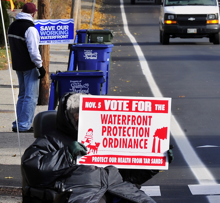 Proponents and opponents hold up dueling signs about South Portland's proposed Waterfront Protection Ordinance on Tuesday as voters head to the polls to decide its fate.