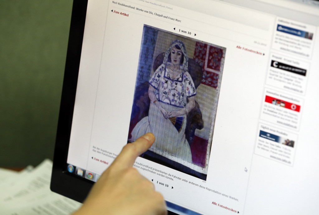 "A researcher for the Art Loss Register in London points to a picture on a news website showing a painting by Henry Matisse titled ""Sitting Woman,"" which is part of the art recently found in Munich, Germany."