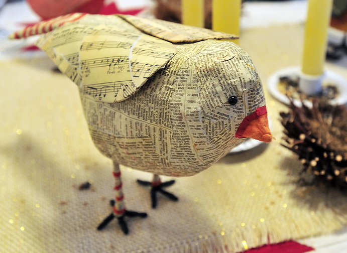 Interior designer Kim Corwin created a dining table centerpiece that featured a flock of papier-mache birds, like this one, complete with birdseed candlestick holders.