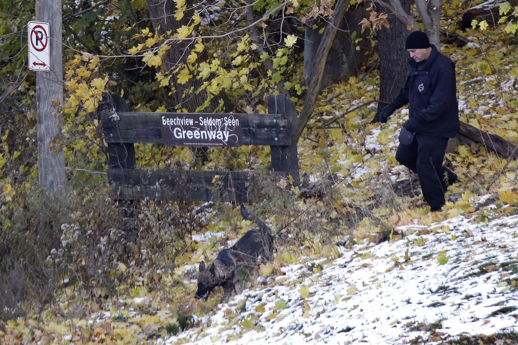 A Pittsburgh police K-9 officer comes out of the woods near the scene where three students were shot outside Brashear High School on Wednesday in Pittsburgh. Police were searching for at least one gunman in some nearby woods and the neighborhood surrounding the school, school and police officials said. Six people were brought in for questioning.