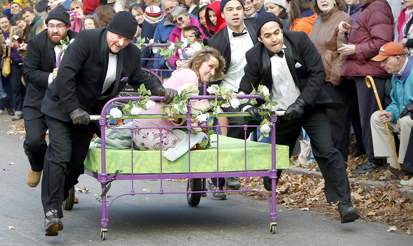 """Wendy Herrick, owner of Wendy Herrick Floral Designs and Tuxedo Rentals, clings to her """"Bed of Roses"""" Saturday as teammates push it to the finish line to win this year's Rolling Slumber Bed Races in Brunswick."""