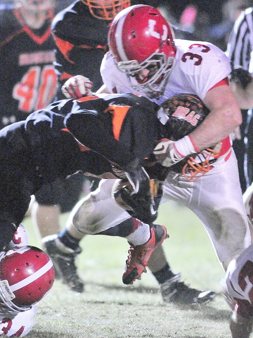 Cony Ram Reid Shostak (33) makes a tackle during the Pine Tree Conference class B championship against Brunswick on Friday in Brunswick.