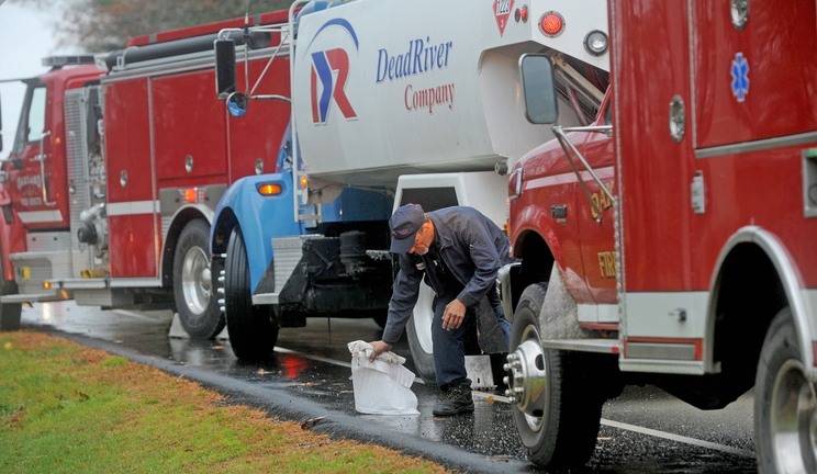 Shawn Mullen, 46, a delivery driver for Dead River Company, mops up spilled fuel in front of 256 Belgrade Road in Oakland on Friday. The delivery truck apparently leaked oil for about six miles through Oakland while making deliveries.