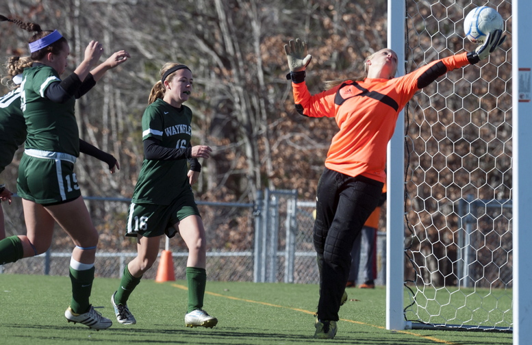 Orono keeper Victoria Goodwin tries to control Esme Benson's shot in the second overtime Saturday, but as she fell the ball went over the line and Waynflete retained the Class C crown. In on the play are Ella Millard, left, and Leigh Fernandez.