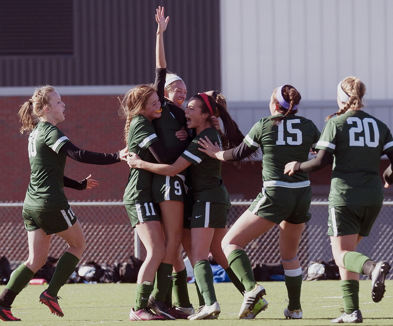 Esme Benson is mobbed by teammates Arianna Giguere (10), Christian Rowe (11), Sofia Canning; Ella Millard (15), and Cat Johnson (20). Benson scored in the second overtime to give Waynflete a 3-2 victory against Orono in the Class C state final.