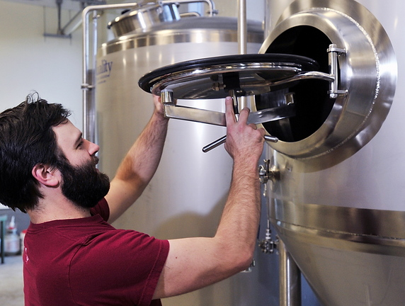 Ian McConnell, an owner and brewmaster of Banded Horn Brewing Co., checks his primary fermenter on Friday. The arrival of the company is seen as a positive economic sign for Biddeford.