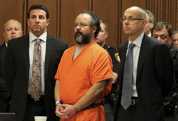 Ariel Castro, 53, stands between attorneys Craig Weintraub, left, and Jaye Schlachet as his sentence is read by Judge Michael Russo in the courtroom in Cleveland, Ohio, on Aug. 1. The judge sentenced Castro to life in prison for abducting, raping and holding captive three women for as long as 11 years, and murder for forcing one of the women to abort her pregnancy. Russo imposed the sentence after an emotional court hearing at which one of Castro's victims, Michelle Knight, 32, said the former school bus driver put her through a life of hell.