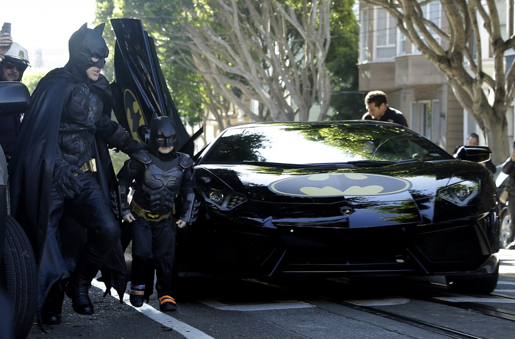Miles Scott, dressed as Batkid, exits the Batmobile with Batman to save a damsel in distress in San Francisco, on Friday.