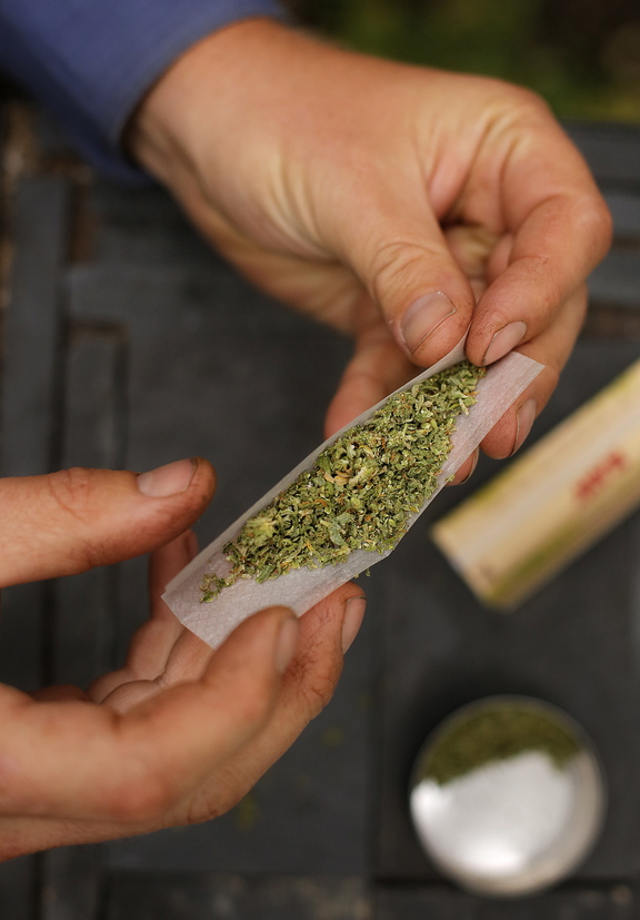 A smoker rolls a marijuana cigarette in Portland last month. The city's electorate legalized recreational use of the drug last week, but federal and state laws still trump the local change.