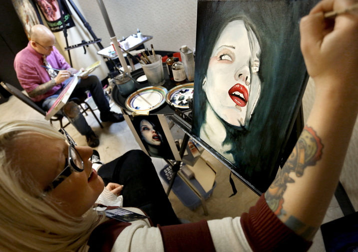 Artist Lila Rees works on an untitled piece alongside artist Chris Dingwell during Coast City Comicon.
