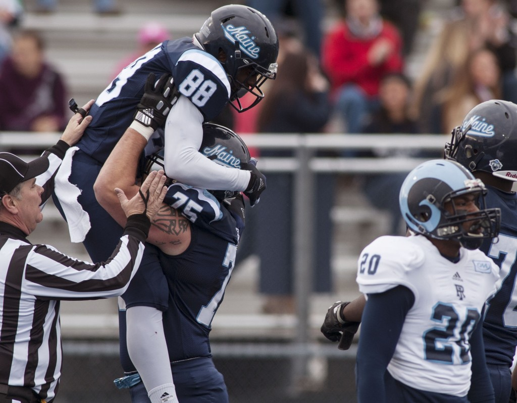 Maine wide receiver DamarrAultmann, 88, celebrates with teammate Joseph Hook after scoring against Rhode Island in the first half on Saturday at Orono. UMaine won 4-0 to clinch the Colonial Athletic Association title.