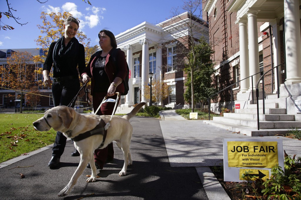 Marie Hennessy, president of the Perkins School for the Blind alumni association, leaves a job fair for the visually impaired accompanied by her guide dog, Azalea,, and a volunteer guide, left, on the Radcliffe Yard campus in Cambridge, Mass. Despite technological advances that dramatically boost their capabilities, blind people remain largely unwanted in U.S. workplaces. About 24 percent of working-age Americans with visual disabilities hold full-time jobs.