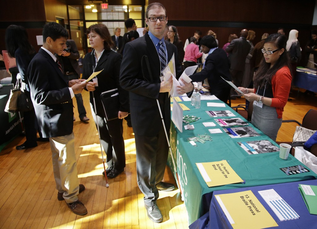 Jeff Paquette, center, a graduate of Johnson and Wales University, waits to speak to a recruiter during a job fair for the visually impaired on the Radcliffe Yard campus in Cambridge, Mass. Paquette is searching for a position in the hospitality industry.