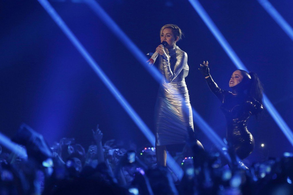Miley Cyrus, left, and a dancer perform at the 2013 MTV Europe Music Awards in Amsterdam, Netherlands, Sunday, Nov. 10, 2013.