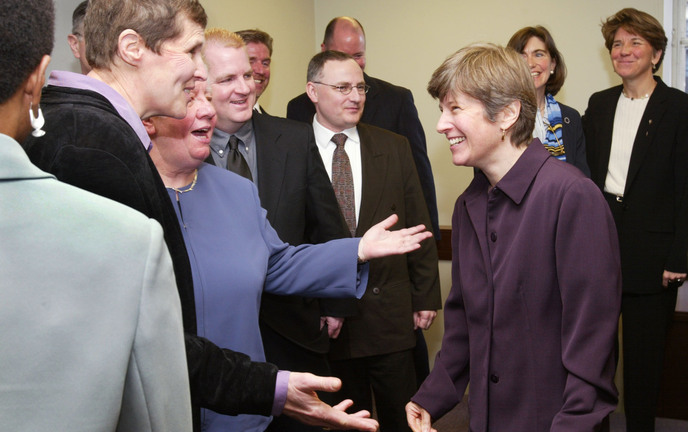 Attorney Mary Bonauto, right, smiles while surrounded by gay couples on March 4, 2003, after a news conference in Boston following oral arguments at the Supreme Judicial Court on their challenge to the state's prohibition on gay marriage.